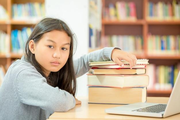 Belle ragazze leggono libri in biblioteche che studiano molto per leggere molti libri