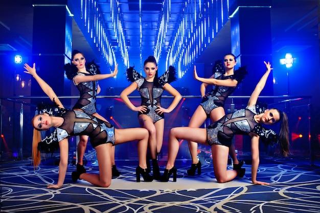 Belle ragazze sexy del ballerino di go-go che propongono al night-club