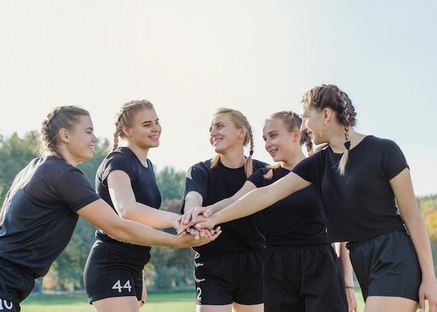 Belle ragazze sportive che uniscono le mani