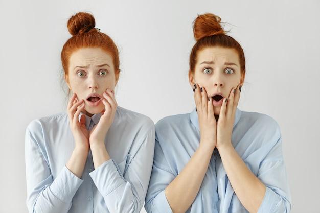 Belle ragazze studentesse europee rosse in camicie formali simili con espressioni scioccate e spaventate