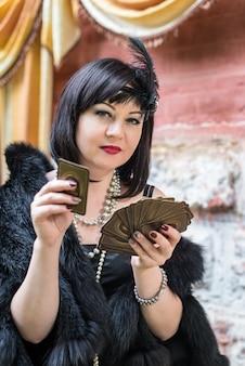 Belle retro carte da gioco della tenuta della donna
