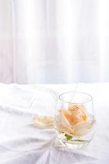 Belle rose beige fresche di testa in vetro su sfondo chiaro.