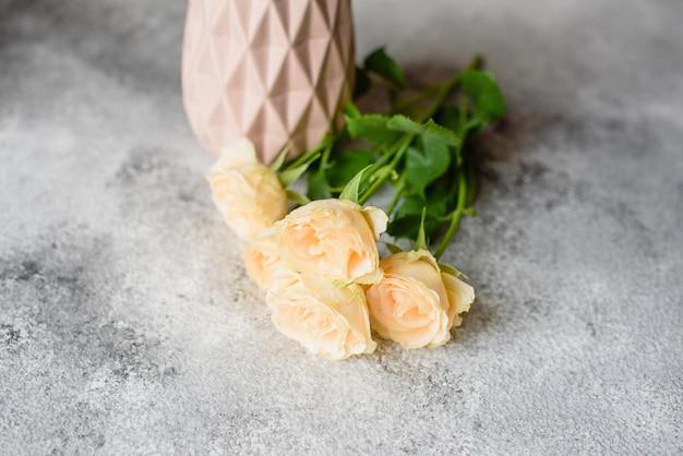 Belle rose beige fresche in un vaso di argilla su uno sfondo concreto. posa e decorazione di un tavolo