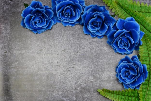 Belle rose blu su uno sfondo con foglie verdi per la vacanza