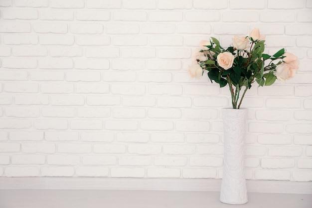 Belle rose e vasi sul muro di mattoni