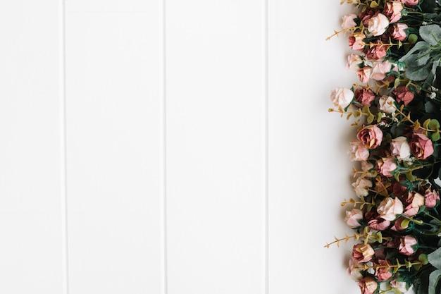 Belle rose su grande fondo in legno bianco con spazio a destra