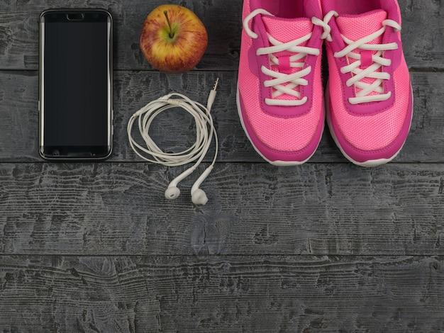 Belle scarpe da ginnastica rosa, cuffie, acqua e mele su un pavimento di legno nero. vista dall'alto