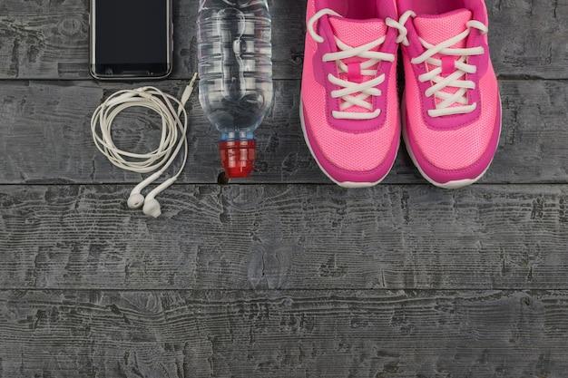 Belle scarpe da ginnastica rosa, cuffie, acqua e mele su un pavimento scuro in legno. vista dall'alto