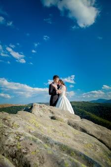 Belle sposi che abbracciano su rocce e montagne. sposa alla moda e bella sposa sono in piedi sulla scogliera. ritratto di nozze. foto di famiglia