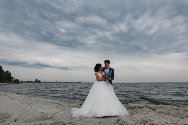 Belle sposi felici sposi al giorno delle nozze all'aperto in spiaggia