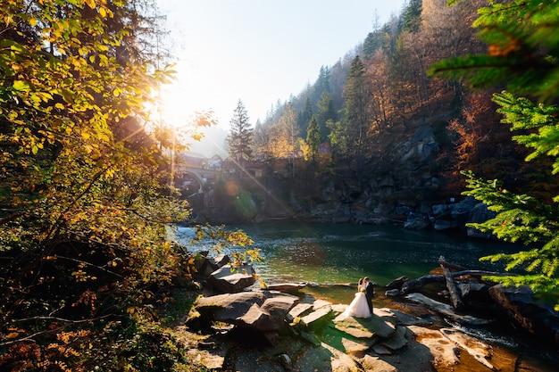 Belle sposi su uno sfondo di rocce e un fiume