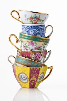 Belle tazze inglesi classiche di caffè e del tè che formano una torre, isolata su bianco.