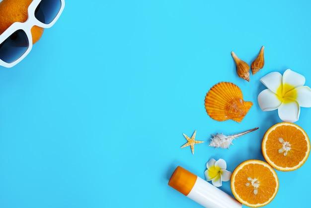 Belle vacanze estive, accessori da spiaggia, arancio, conchiglie e crema solare