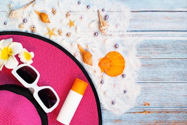 Belle vacanze estive, accessori da spiaggia, occhiali da sole, cappello e conchiglie su legno