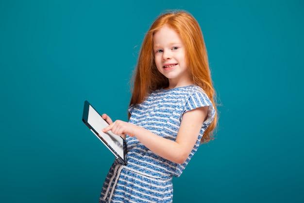 Bellezza bambina in t-shirt con i capelli lunghi, con tavoletta in mano
