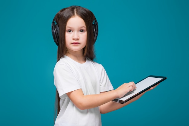 Bellezza bambina in t-shirt e auricolari con i capelli lunghi, con tavoletta in mano