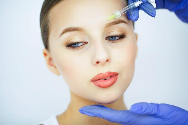 Bellezza e cura. ritratto di una giovane donna con un bel viso. un cosmetologo fa le iniezioni. alta risoluzione