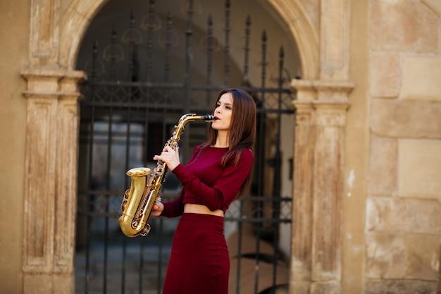 Bellezza e moda, musica. donna graziosa con il sassofono.