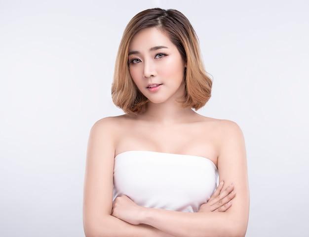 Bellezza giovane donna asiatica con perfetta pelle del viso. gesti per trattamenti termali pubblicitari e cosmetologia.