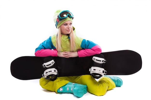 Bellezza giovane donna in tuta da sci e occhiali da sci sedersi con sbowboard