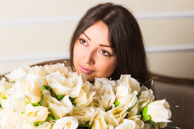 Bellezza moda modello volto di donna. ritratto con fiori di rosa bianca. bella donna bruna con trucco di lusso, pelle perfetta. san valentino