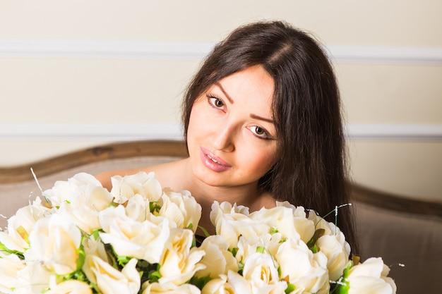 Bellezza moda modello volto di donna. ritratto con fiori di rosa bianca.