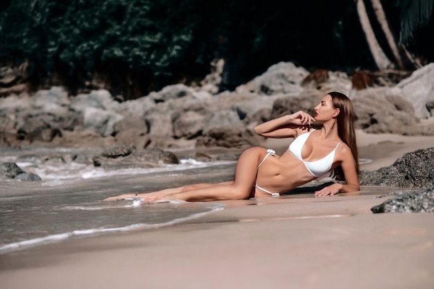 Bellezza tropicale in una spiaggia di riposo del costume da bagno bianco. vacanze estive