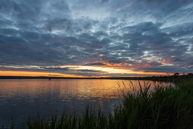 Bellissima alba sul fiume, prima dell'alba, con parte della riva e canne