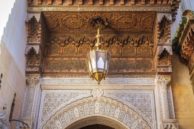 Bellissima arte marocchina. soffitto intagliato in legno, lampada antica e arabesque sul muro.