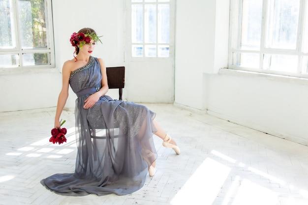 Bellissima ballerina seduta in abito lungo grigio
