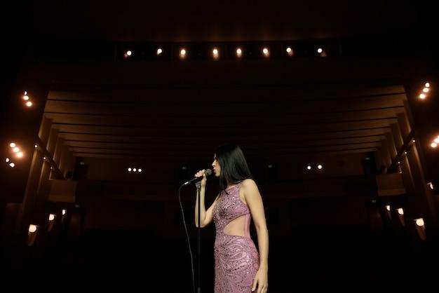 Bellissima cantante contro l'auditorium. vista posteriore donna in abito lungo esibirsi sul palco