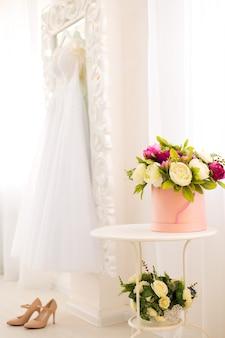 Bellissima composizione con peonie colorate in una scatola rotonda, tacchi alti e abito da sposa