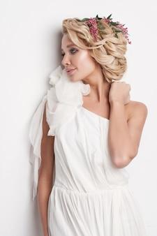 Bellissima giovane donna con delicati fiori tra i capelli