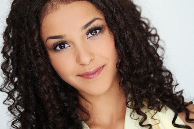 Bellissima giovane donna con i capelli ricci neri