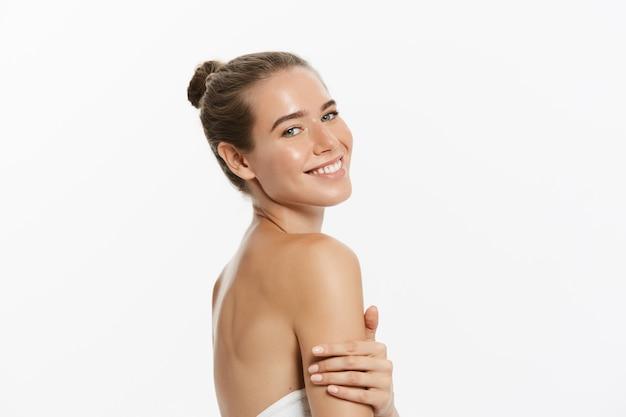Bellissima giovane donna con la pelle pulita fresca tocco proprio viso. trattamento facciale.