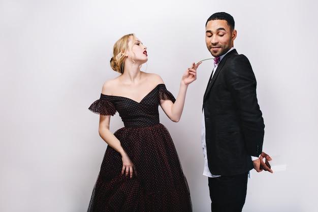 Bellissima giovane donna in abito da sera con fiore guardando maliziosamente bell'uomo in smoking con presente dietro la schiena. giocoso coppia adorabile, san valentino, sorpresa.