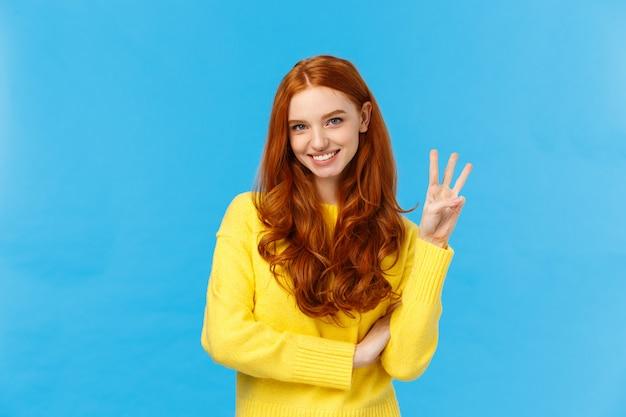 Bellissima giovane donna rossa 20s in maglione giallo, sorridente spensierato, prenotazione