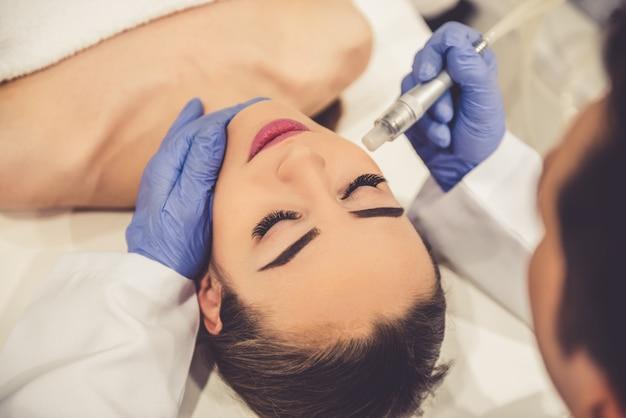 Bellissima giovane donna sta ricevendo un trattamento per la pelle del viso.
