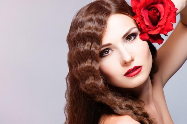 Bellissima giovane modella con labbra rosse e rosa rossa