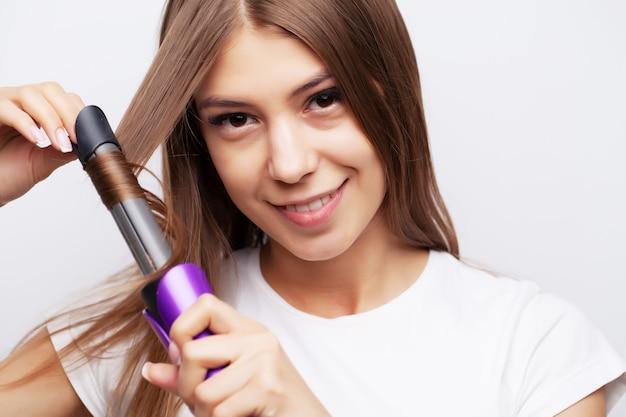 Bellissima giovane modella femmina si prende cura dei suoi capelli e usa una piastra per capelli
