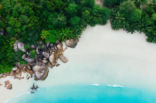 Bellissima isola alle seychelles. la digue, anse d'argent beach. scorrimento dell'acqua e schiuma delle onde su un paesaggio tropicale