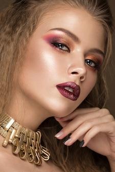 Bellissima modella bionda con trucco luminoso, gioielli d'oro e labbra rosse.