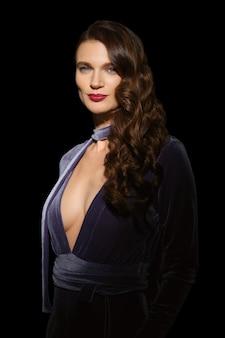 Bellissima modella con pelle pulita e sana e in abito di velluto in posa nella stanza buia