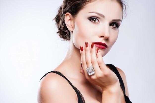 Bellissima modella giovane con labbra rosse e manicure rossa