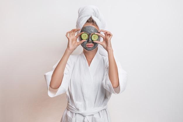 Bellissima modella in posa in un accappatoio e un asciugamano sulla testa tenendo cetrioli sugli occhi con una maschera di argilla sul viso