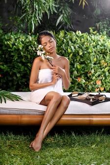 Bellissima modella interrazziale in posa con un rametto di fiori bianchi vicino al viso in un asciugamano di spugna su un lettino da massaggio su cui si trova un vassoio per la terapia termale