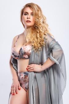 Bellissima modella plus size che indossa lingerie e tessuto pezzo
