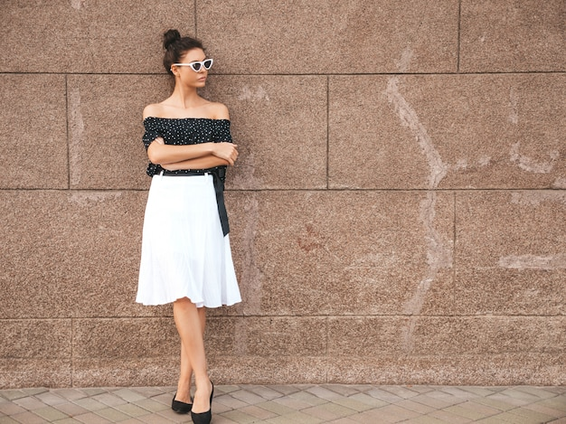 Bellissima modella vestita in eleganti abiti estivi ragazza sexy spensierata in posa in strada vicino al muro. donna di affari moderna alla moda in occhiali da sole divertendosi