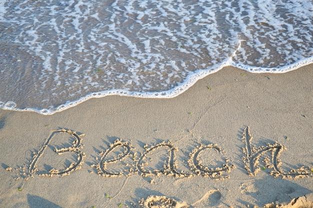 Bellissima spiaggia di sabbia e morbida onda blu oceano e testo spiaggia