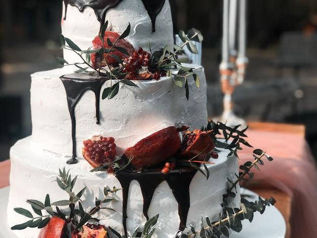 Bellissima torta nuziale bianca a tre strati con frutti di melograno e fiori freschi